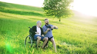 An adult hipster son and senior father in wheelchair using binoculars in nature at sunset.