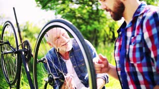 An adult hipster son and senior father repairing bicycle outside on a sunny summer day. Slow motion.