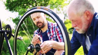 An adult hipster son and senior father repairing bicycle outside on a sunny summer day, talking. Slow motion.
