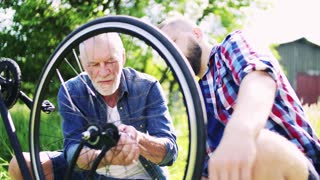 An adult hipster son and senior father repairing bicycle outside on a sunny summer day.