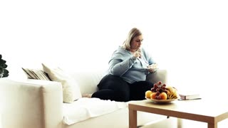 An attractive blond overweight woman at home, eating cake.