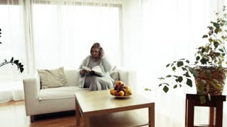 An attractive blond overweight woman at home, reading a book.