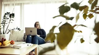 An attractive blond overweight woman with laptop at home, typing.