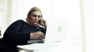 An attractive blond overweight woman with smartphone and laptop at home, making a phone call and writing.