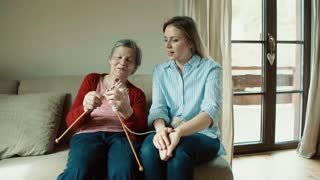 An elderly grandmother and adult granddaughter at home, knitting. Slow motion.