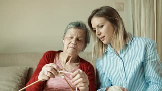 An elderly grandmother and adult granddaughter at home, knitting.