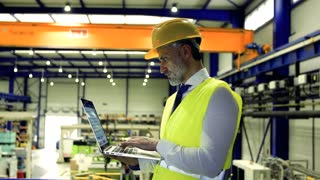 An industrial man engineer standing in a factory, using laptop. Copy space.