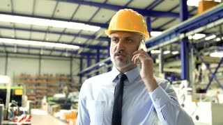 An industrial man engineer with smartphone walking in a factory, making a phone call.