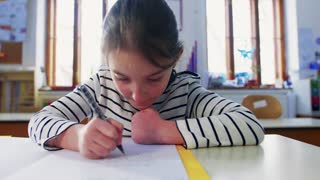 An small girl sitting at the desk at school writing. Close up.