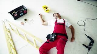 An unconscious man worker lying on the floor after an accident at work on the construction site. Top view. Slow motion.