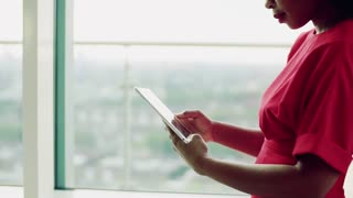 An unrecognizable woman standing in an office by the window in an office, using tablet. Copy space. Slow motion.