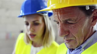 Architect, civil engineer and worker discussing issues at the construction site. Close up.