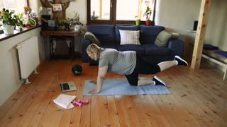 Attractive overweight woman at home exercising on a mat.