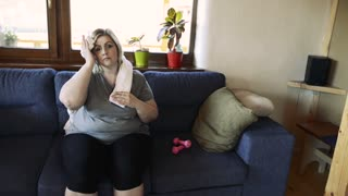 Attractive overweight woman exercising at home, wiping off sweat.