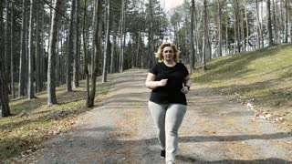 Attractive overweight woman running with a smartwatch