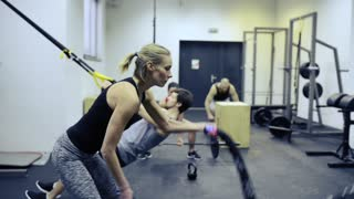 Beautiful blonde woman doing intense strength training, working out with battle ropes at gym.