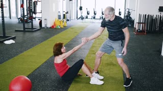 Beautiful fit senior couple in modern crossfit gym.