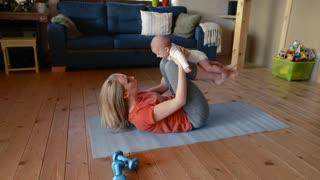 Beautiful fit young mother does crunches together with her little baby son at home.