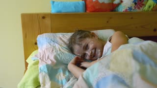 Beautiful little girl at home lying in bed sick with chickenpox, white antiseptic cream applied to the rash on her face.