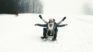 Beautiful senior couple on sledge having fun, winter day.
