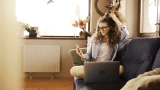 Beautiful teenage girl sitting on couch holding smart phone, reading something, laptop laid next to her.
