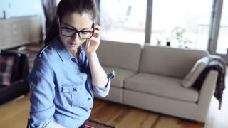 Beautiful woman working from home, making a phone call.