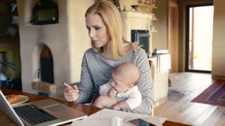 Beautiful young blond mother at home with her little baby son in the arms, sitting at the table, working on laptop, writing something