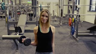 Beautiful young blond woman in gym working her arms with weights