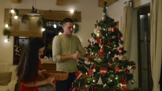 Beautiful young couple decorating Christmas tree at home.