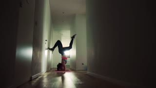 Beautiful young fitness woman doing exercise at home. Handstand balancing.