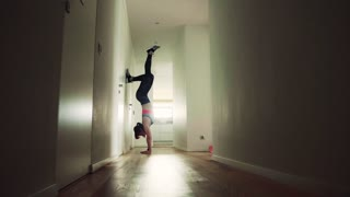 Beautiful young fitness woman doing exercise at home. Handstand.