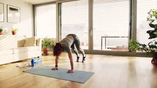 Beautiful young fitness woman doing exercise at home. Slow motion.