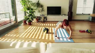 Beautiful young fitness woman doing pushups exercise at home. Slow motion.