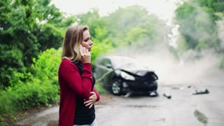 Beautiful young woman making a phone call after a car accident, smoke in the background.