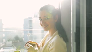 Beautiful young woman relaxing on balcony with city view holding a cup of coffee or tea, enjoying a hot drink
