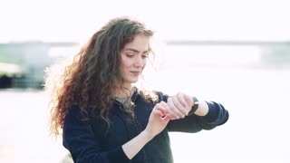 Beautiful young woman standing outside in the city, using smartwatch. Slow motion.