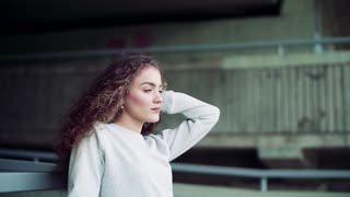 Beautiful young woman standing under the bridge in the city. Slow motion.