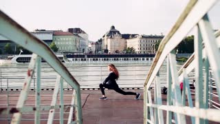 Beautiful young woman stretching outside by the river in the city. Slow motion.