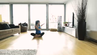 Beautiful young woman working out at home in her living room, doing yoga or pilates exercise, sitting on the floor stretching legs, arms and back