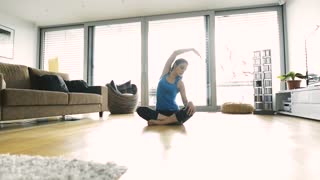 Beautiful young woman working out at home in her living room, doing yoga or pilates exercise, stretching arms and back, sitting on the floor with legs crossed.