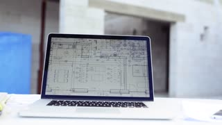 Blueprints and laptop on construction site.