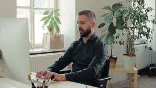 Businessman in wheelchair working in the office. Slow motion