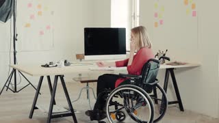 Businesswoman in wheelchair with smartphone sitting at the desk, making notes