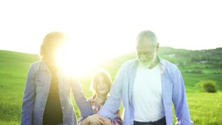 Cheerful senior couple with granddaughter outside in spring nature at sunset, walking and talking.