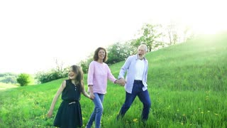 Cheerful senior couple with granddaughter outside in spring nature, walking. Slow motion.