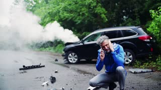 Close-up of a frustrated mature man making a phone call after a car accident, smoke in the background. Slow motion.
