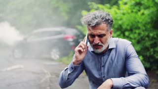 Close-up of a frustrated mature man making a phone call after a car accident, smoke in the background.