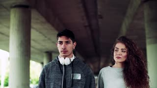 Close-up of a young couple walking under the bridge in the city. Slow motion.
