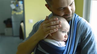 Close up of young father with his newborn baby son in sling at home, caressing and kissing him