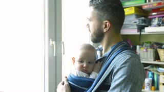 Close up of young father with his newborn baby son in sling at home